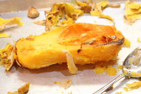 Cut off the papery skin from the butternut squash after roasting.